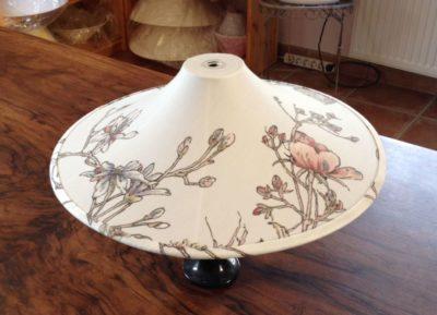 Ein Lampenschirm in der Form eins China-Hütchen aus gemustertem Baumwollstoff.