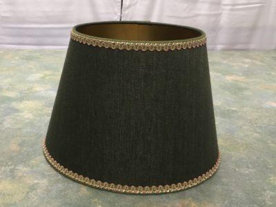 Dunkelgrüner Stoff auf goldglänzender Kaschierfolie aufgebracht und mit Bortenbesatz.