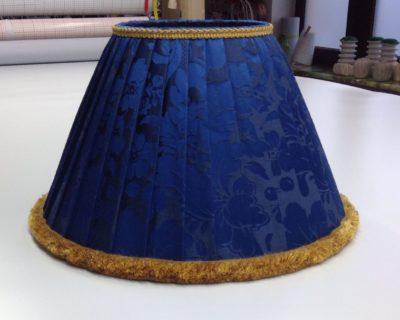 Ein Lampenschirm aus exklusiver Seide mit kontrastreichem Bortenbesatz.