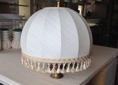 Ein kuppelförmiger Lampenschirm aus Naturfaserstoff mit tradioneller Fransenborte.