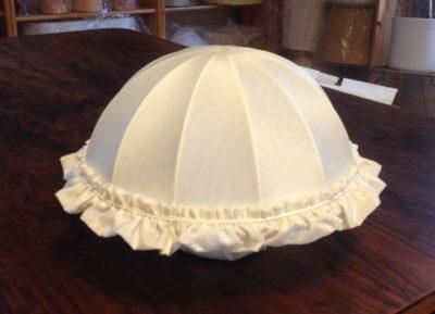 Ein kuppelförmiger Lampenschirm mit gerüschtem Randbesatz.