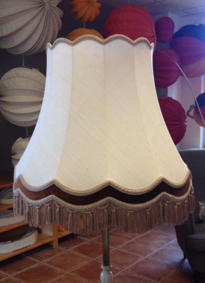 Ein neu bespannter Lampenschirm mit Baumwollstoff sowie Samtspiegel und Bortenbesatz.