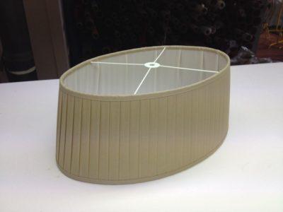 Ein plissierter ovaler Lampenschirmschirm aus Baumwolle mit weißen Innenfutter.