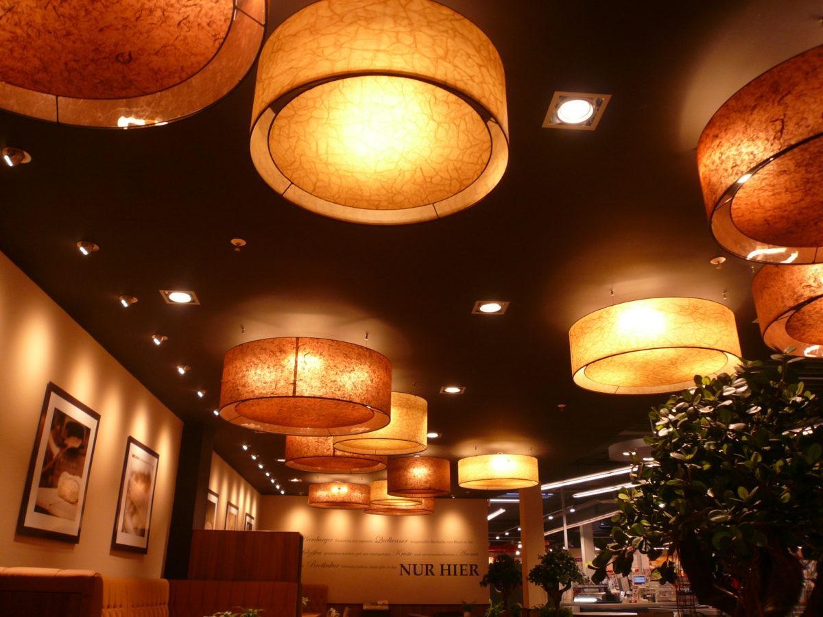 Große zylindrische Lampenschirme aus Lampenschirmmaterial in warmen Brauntönen.