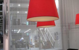 Große konische Lampenschirme aus Stoff auf weißer Kaschierfolie mit schlicht umgeschlagenen Kanten.