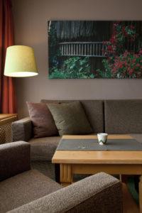 Der grüne kaschierte konische Lampenschirm fügt sich harmonisch in die Einrichtung ein.