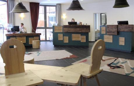 Überdimensional große Filzhüte in unterschiedlichen Ausführungen zieren den Empfangsbereich eines Hotels in Oberstdorf.