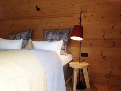 Schlichte Stehlampen mit Lampenschirmen aus rotem Wollfilz als Nachttischbeleuchtung zum Lesen im Bett.