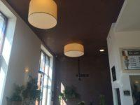 Die zylindrischen Lampenschirme setzen einen tollen Kontrast zu der dunklen Decke.