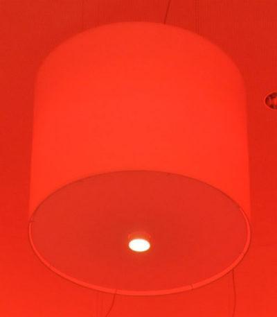 Ein großer zylindrischer Lampenschirm mit RGB Beleuchtung mit unterschiedlichen Lichtfarben und Farbtönen für Lichtspiele.