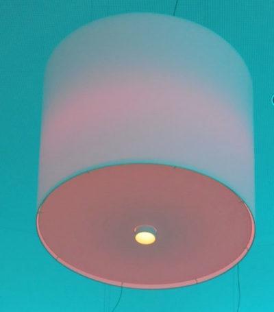 Ein großer zylindrischer Lampenschirm mit RGB Beleuchtung mit unterschiedlichen Lichtfarben.