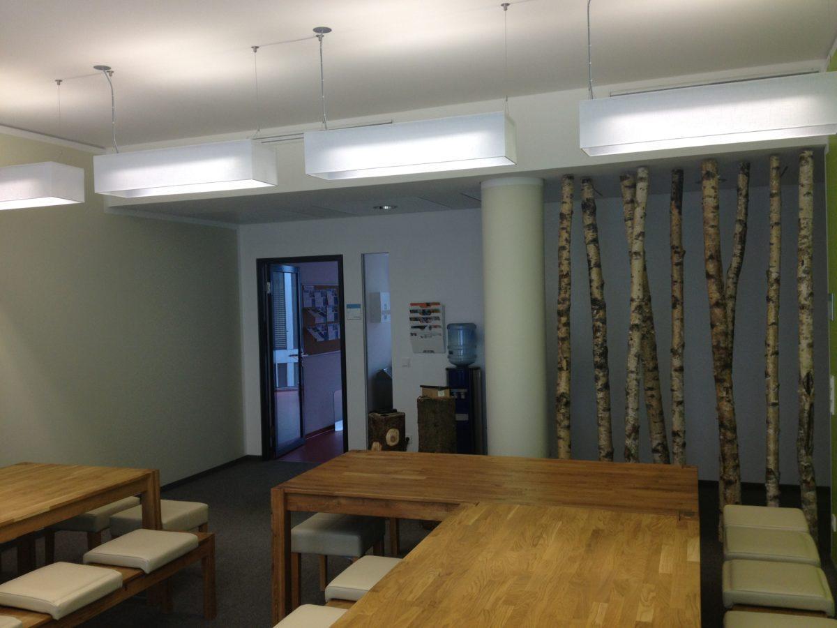 Große rechteckige Lampenschirme als Stülpausführung für vorhandene Lampen in einem Mitarbeiter-Raum mit verschiedenen dekorativen Elementen.